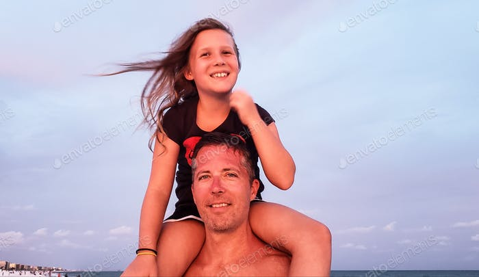 Generation X dad free to walk the beach with a generation Z on his shoulders to social distance them