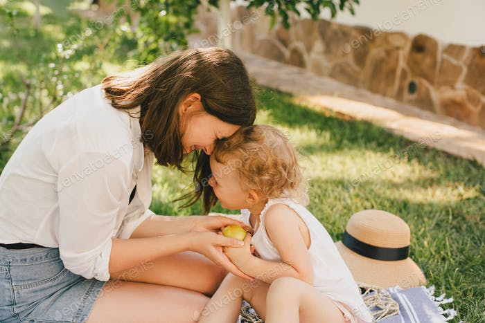 Young mother and her baby having summer picnic together