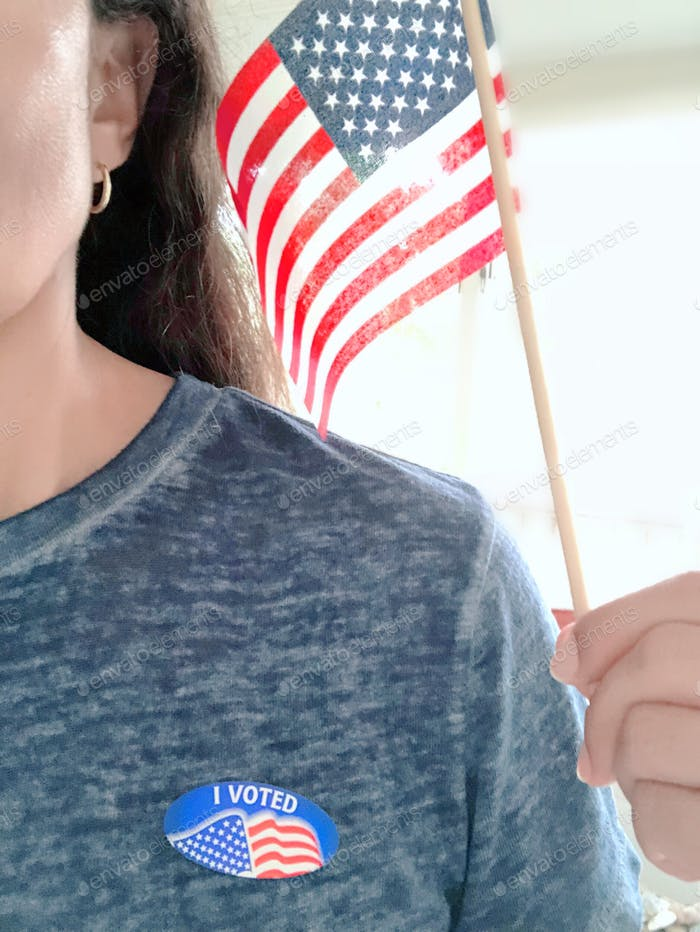 """Latino woman wearing a sticker with """"I voted"""" printed & holding the USA flag."""