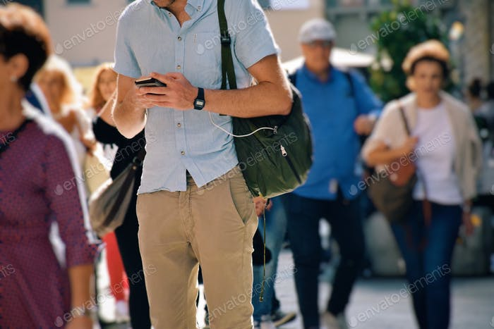 Young man is standing in the middle of a busy city street and using his mobile phone  💲