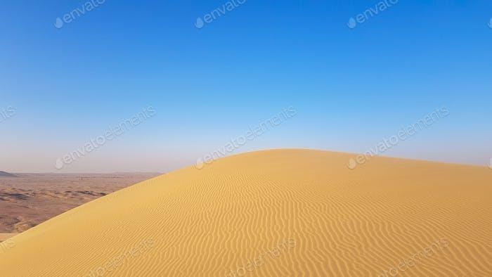 Sand dunes in Qatari Desert. Desert scene. Blue sky. Empty. Background