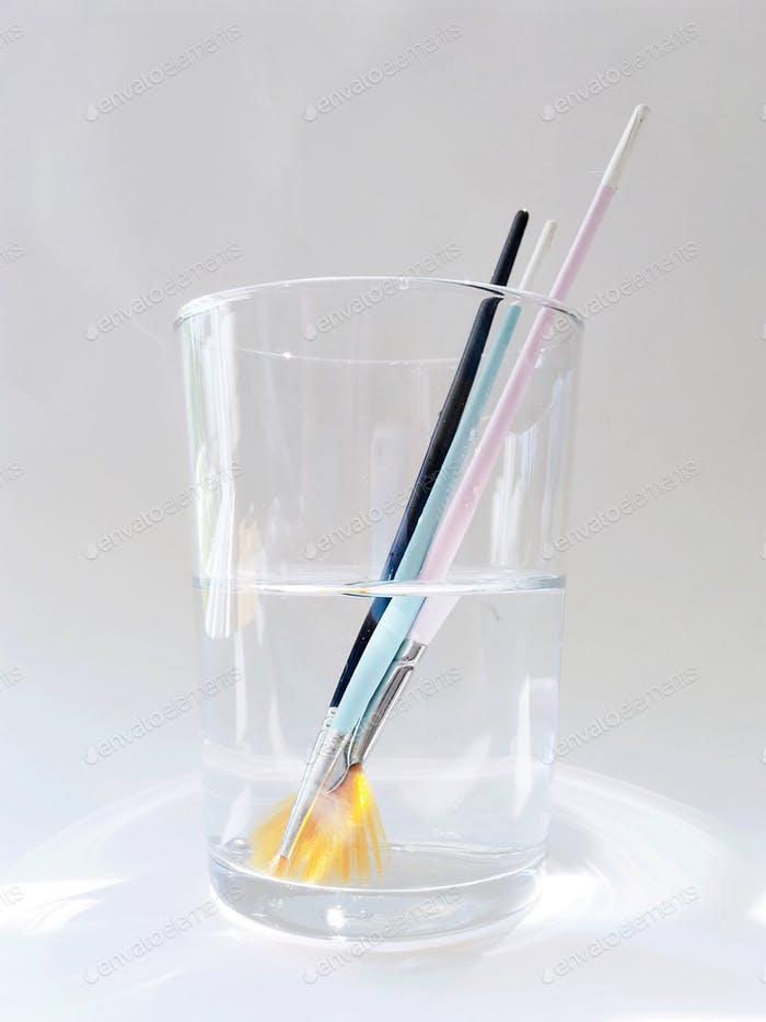 Assortment of colorful artist's paintbrushes leaning in a clear drinking glass of clean water agains