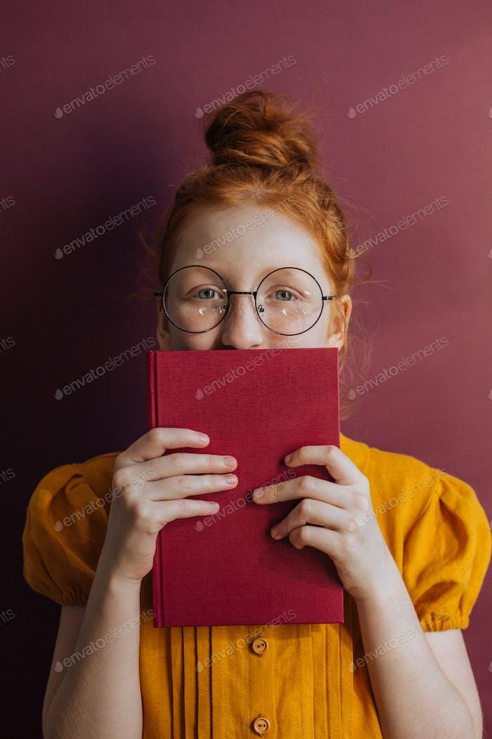 Rothaarige Mädchen in Brille mit einem Buch in ihren Händen auf einem grau-lila Hintergrund.