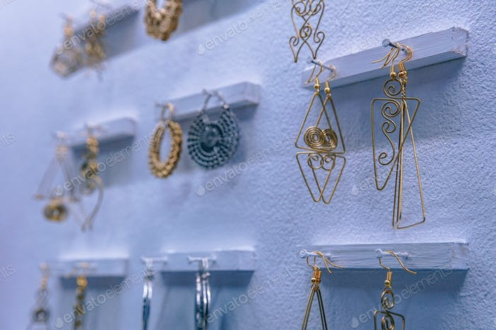Brass Earrings Displayed for Sale on a White Wall
