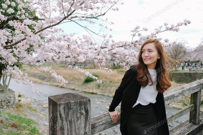 fashion beside river with sakura in kyoto Japan