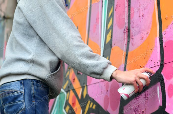 Hand of a young guy in a gray hoodie paints graffiti in pink and green colors on a wall in rainy