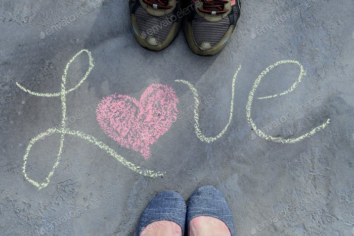Male and female couple feet Standing next to the word LOVE written in script in sidewalk chalk with