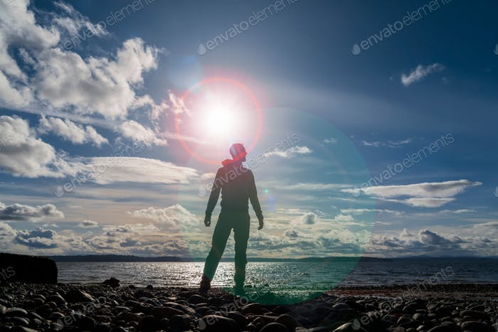 Silhouetted man standing by the sea in lens flare aura