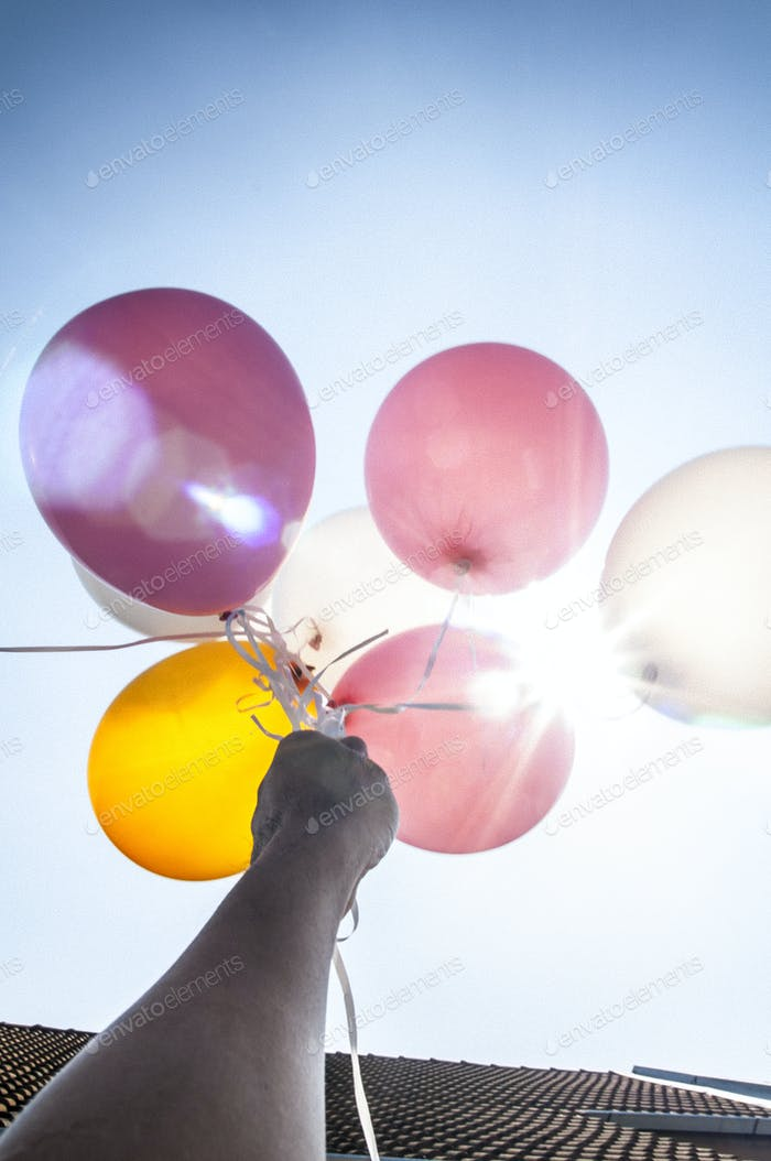 Hand holding colorful balloons up in air with lens flare