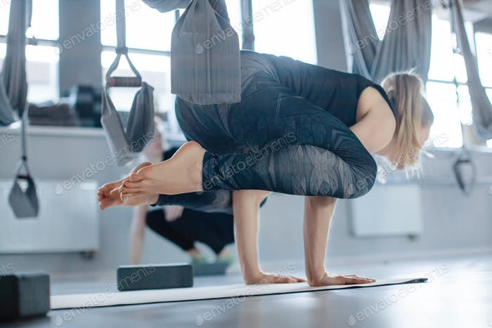 Beautiful athletic young woman doing yoga in the gym. The girl does a handstand, side view
