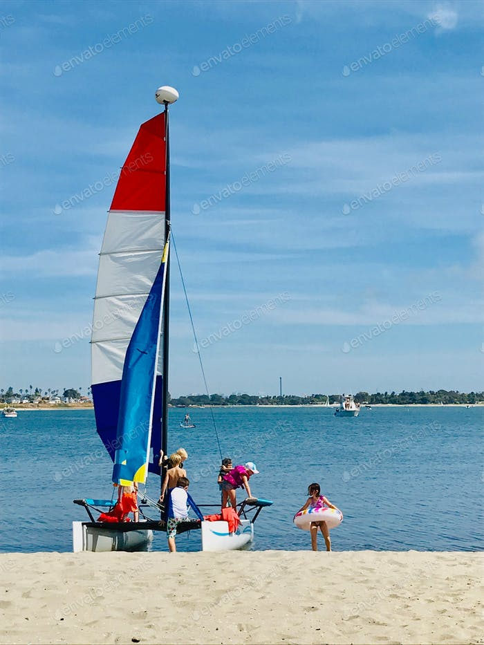 Kids playing on their catamaran on Mission Bay on a sunny day with the famous SeaWorld San Diego