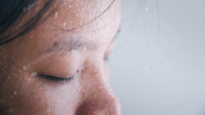 Close up of sweating water drop on face asian woman.