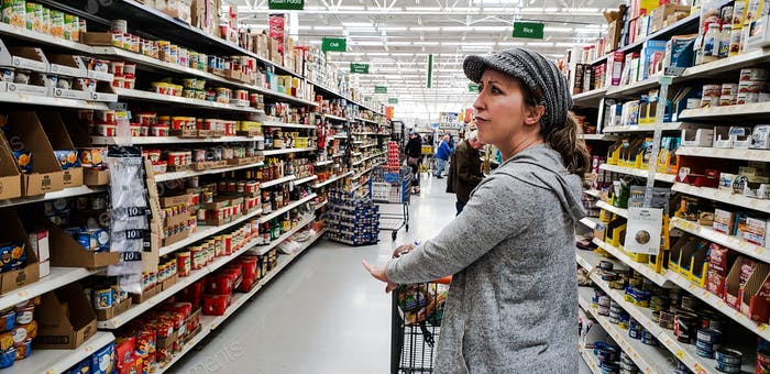 Millenial woman searching for a grocery item she needs in grocery store...