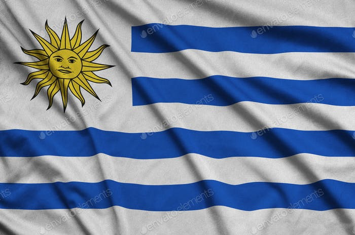 Uruguay flag  is depicted on a sports cloth fabric with many folds. Sport team waving banner