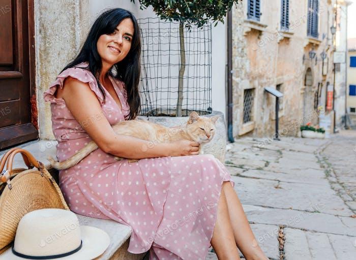 Frau im rosa Kleid streichelt eine süße Ingwerkatze, blickt in die Kamera und lächelt.