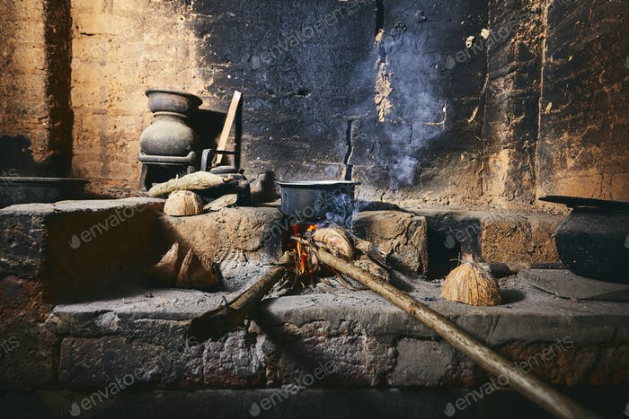 Preparing food on fire pit in traditional home kitchen. Domestic life in Sri Lanka.