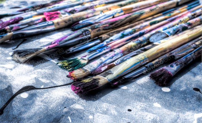 Art Paint brushes. Dried blue, pink, yellow, green paint on paint brushes. Colourful paint brushes