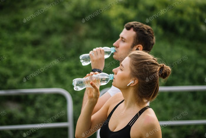 Young couple drinking water from plastic bottle. Man woman runners