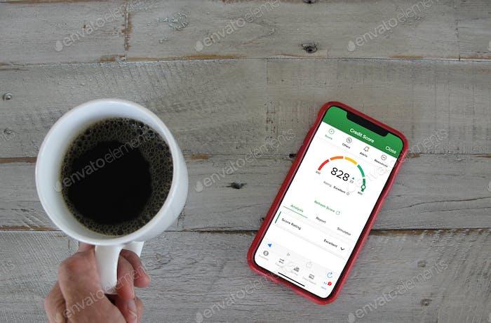 Persona que verifica el puntaje de crédito en la aplicación bancaria en un dispositivo móvil mientras toma café por la mañana