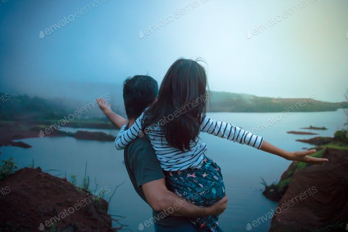 Father and daughter enjoying a scenic view at blue hour