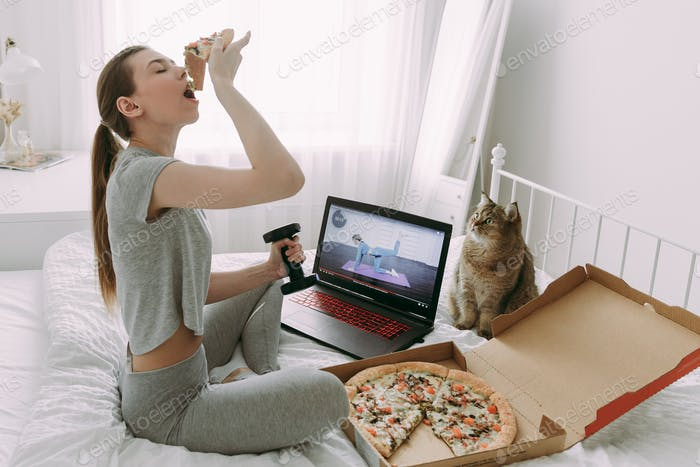 a young girl in quarantine uses a laptop to exercise at home and eats pizza on a bed with a cat