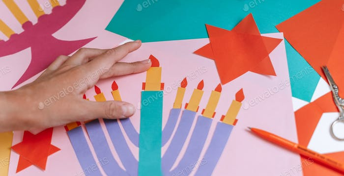 a girl makes a card for happy Hanukkah with her hands, a candelabra and candles on the card