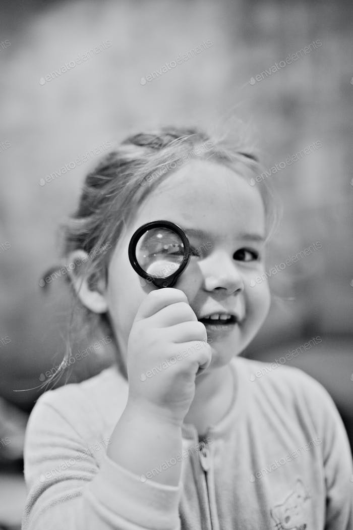 little girl being silly with a looking glass