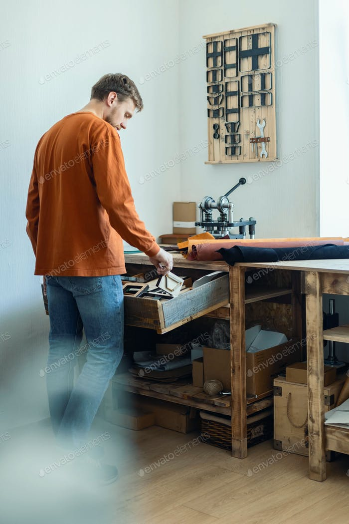 Male tanner working with handpress device machine cutting pattern on stuff material leather workshop