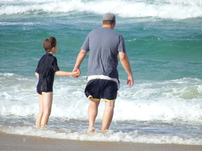 Father and son wading in the waves at the beach