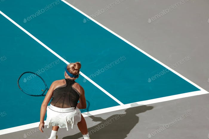female tennis player on court, competitive sport