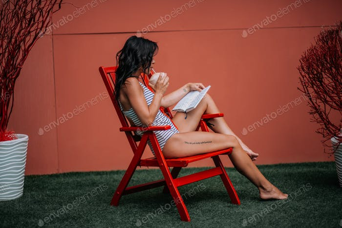 Candid caucasian black hair young adult lady in swimsuit spending summer vacation in the open air