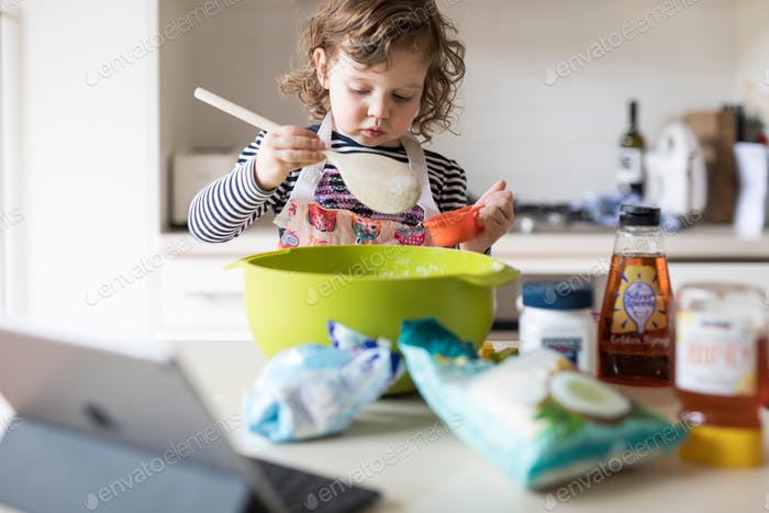 A young girl wearing an apron mixing flour in a bright green bowl in preperation for making fresh co