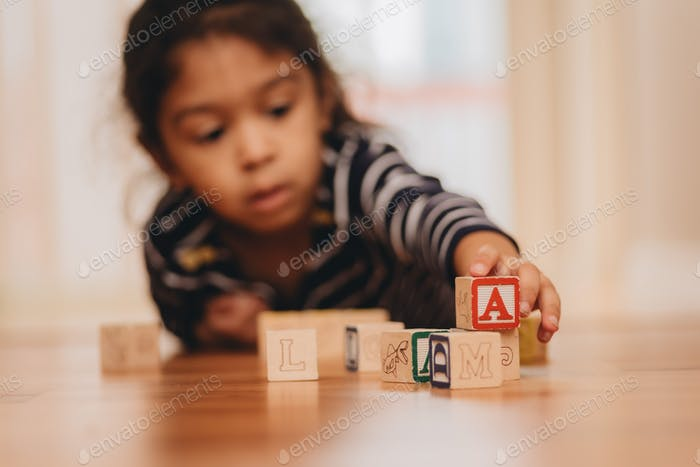 Diverse pre-k girl at home on hardwood floor playing with wooden letter blocks, learning blocks, alp