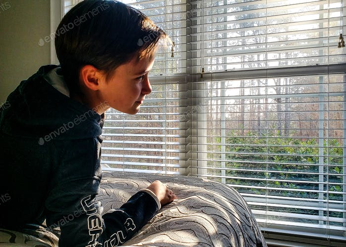 Little boy looking through a window revealing light and shadow...