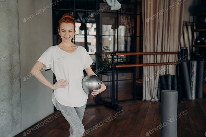 Smiling fit female posing with pilates ball in fitness studio