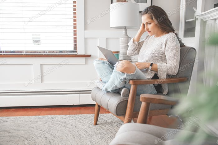 Woman working from home on a laptop in a brightly lit living room