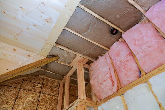 Attic loft insulation partly insulated wall covering view of layers of pink fiberglass barrier