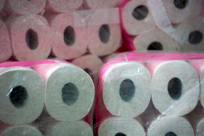 Ein großer Stapel Toilettenpapier. Ein vorrätiges Toilettenpapier mit rosa Aufdruck in der Verpackung.