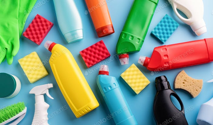 cleaning and housekeeping. collection of various sanitary bottles and cleaning tools on solid blue b