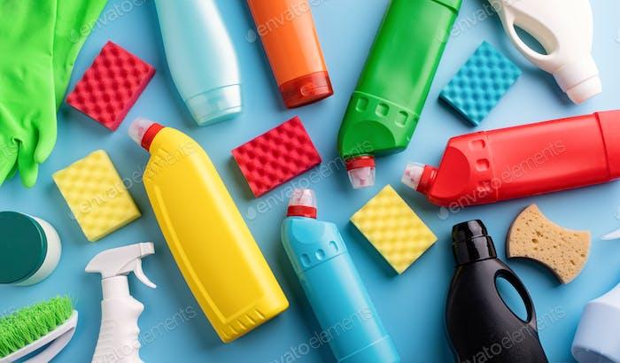Reinigung und Hauswirtschaft. Sammlung von verschiedenen Hygieneflaschen und Reinigungswerkzeugen auf massivem Blau