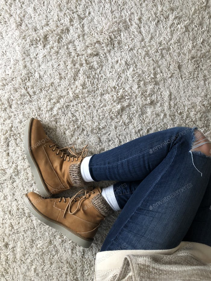 Boots ripped jeans and a sweater