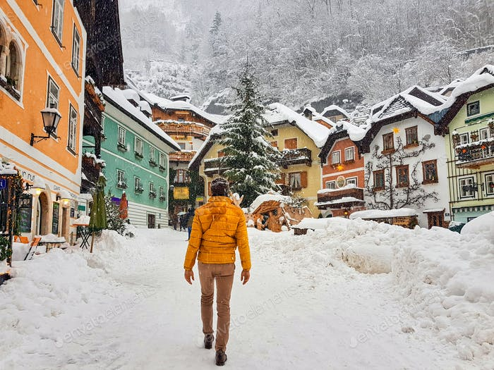 Rear view of man in yellow winter jacket in snow covered town. Hallstatt, Austria.