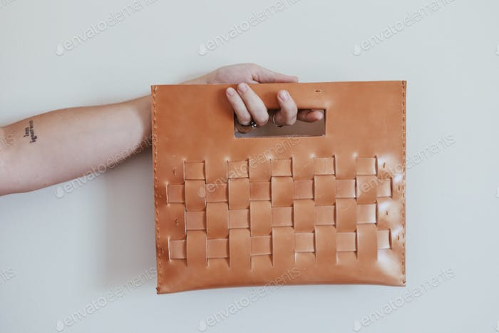 Hand holding leather hand bag