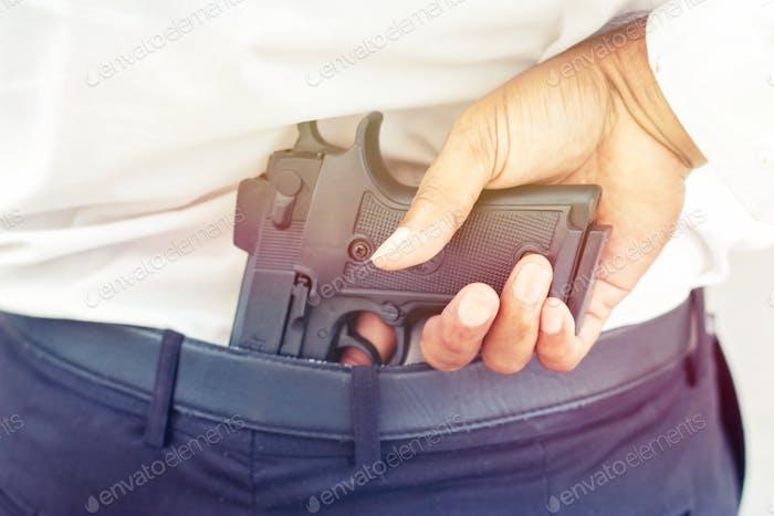 Man is hiding gun at his back.