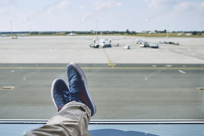 Man waiting at airport. Personal perspective of traveler from window to taxiways and runway.