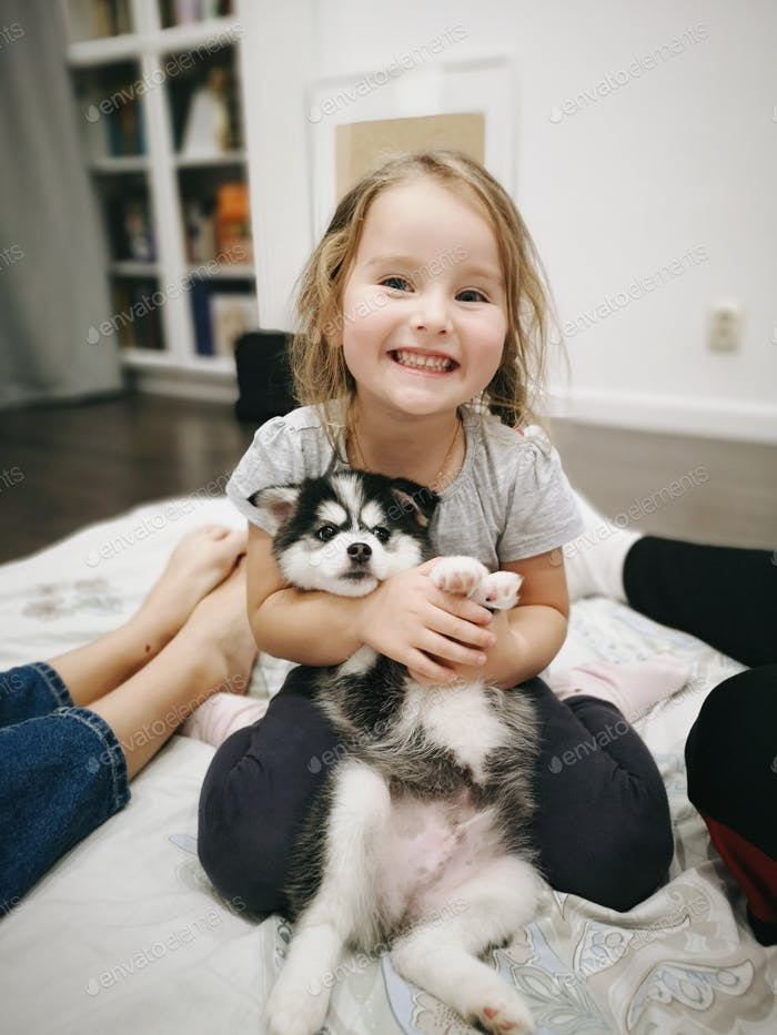 Happiest smiling girl is hugging a puppy