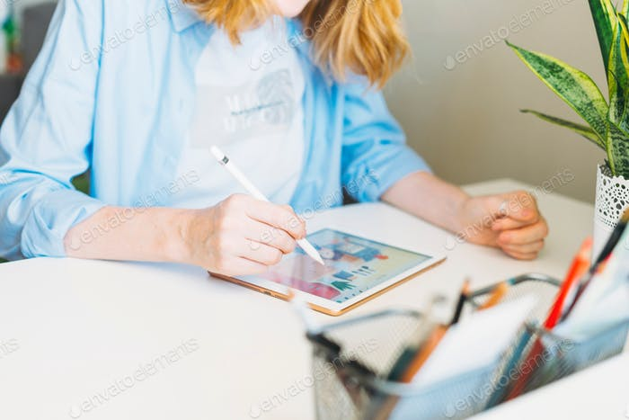 Young woman with red hair illustrator web designer draws on tablet at desk at the home office