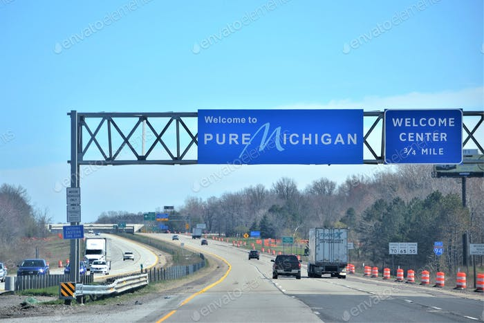 Traveling on the interstate with road signs welcoming you into their state Pure Michigan