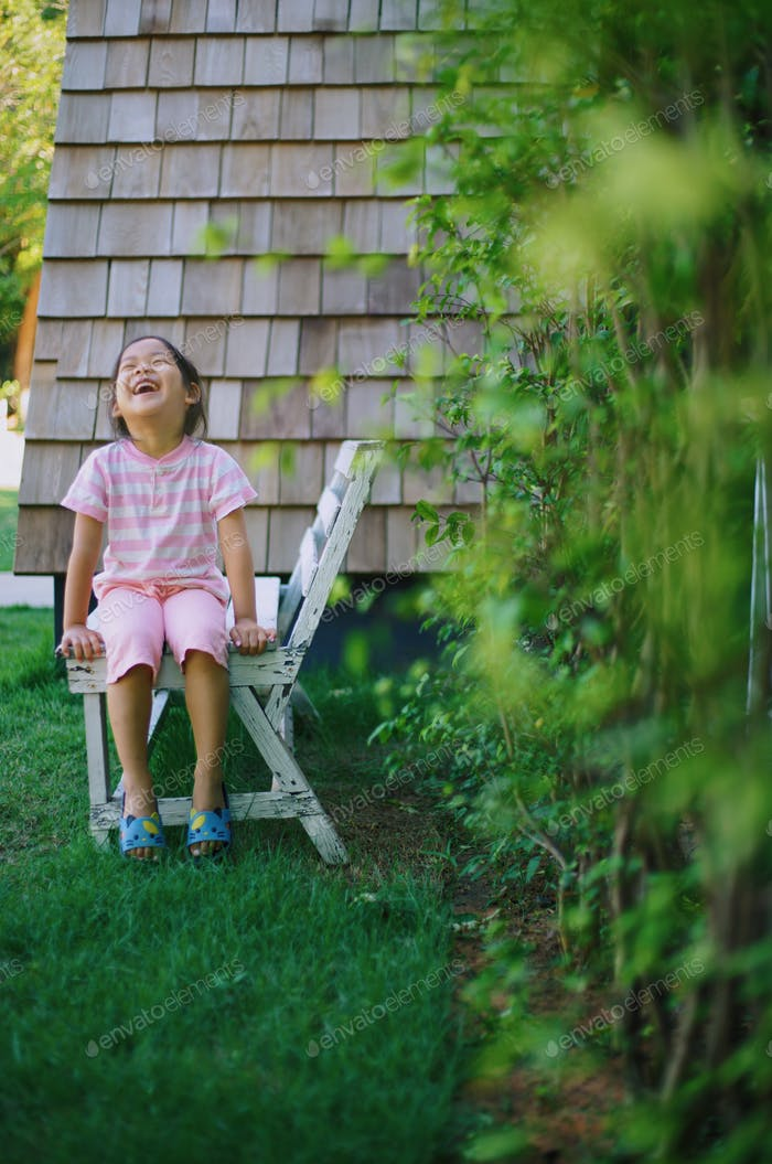 A girl laughing out loud in the backyard