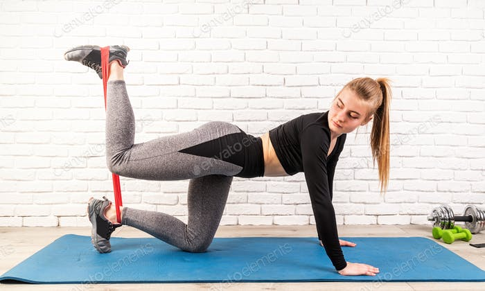Young feet woman working out using a rubber resistance bands